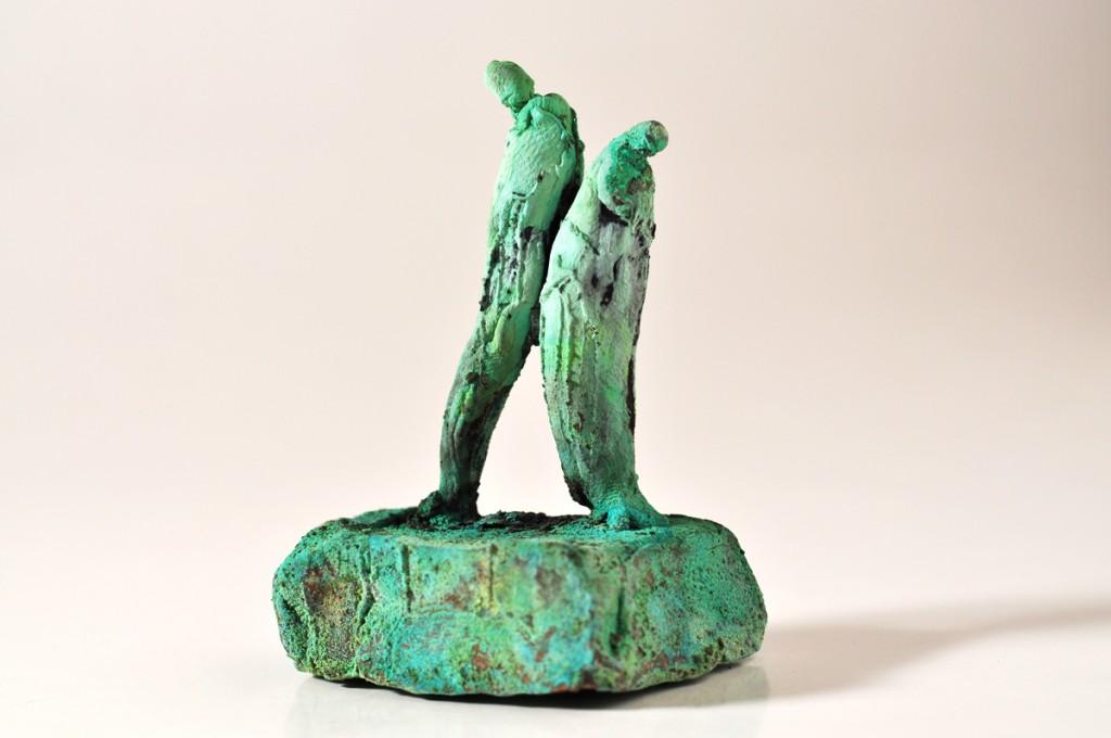 Bronzefigurer der støtter - ryg mod ryg.