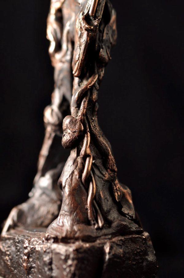 Grounded - bronzefigur med markant udtryk.